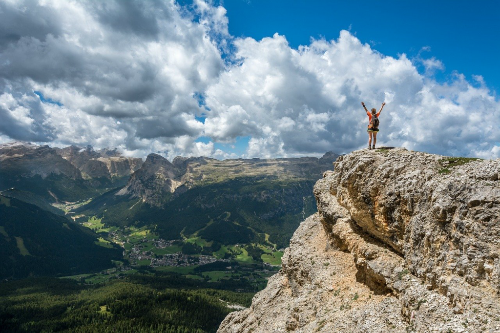 Hiker standing on the top of a mountain with arms outstretched.
