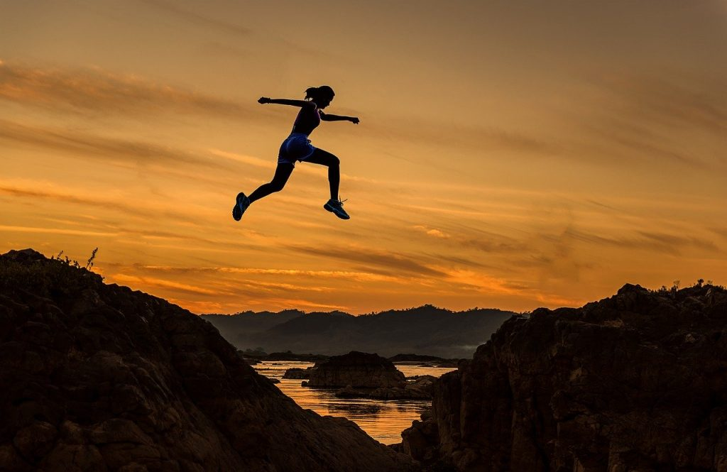 Girl leaping through the air over a crevice during sunset.