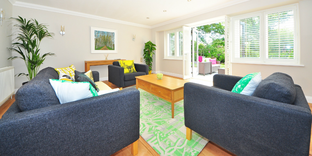 A bright living room with a grey couch and two grey squishy chairs. A bright green carpet lies on the floor with a wooden coffee table on top. Plants are in two corners of the room and large windows reveal a backyard.