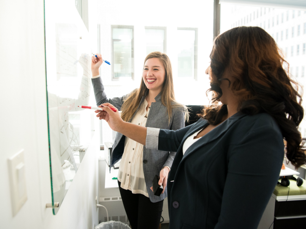 Two happy employees smile as they approach white board with arms raised and holding markers.